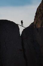 silhouette of a person standing on a board stretched between rock peaks