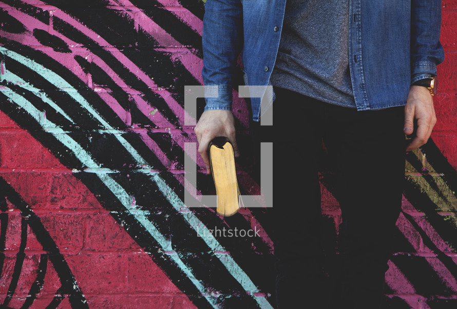 A young man standing in front of a geometric pattern on a wall holding a Bible