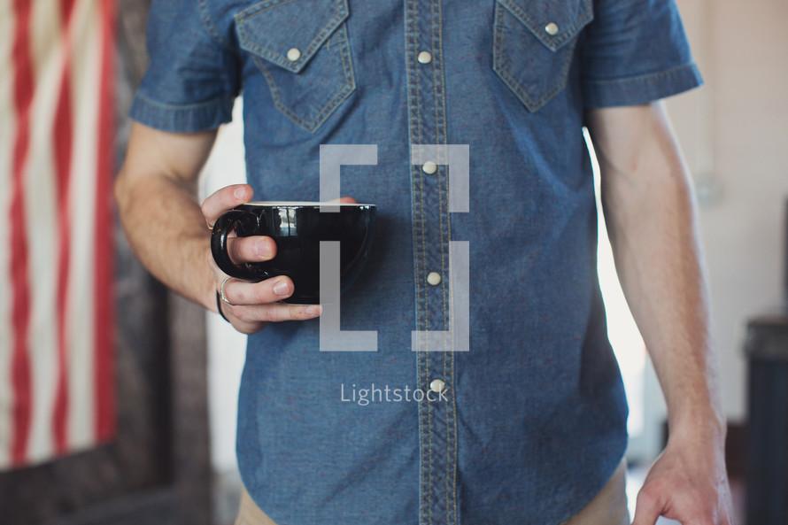 a torso of a man holding a coffee mug