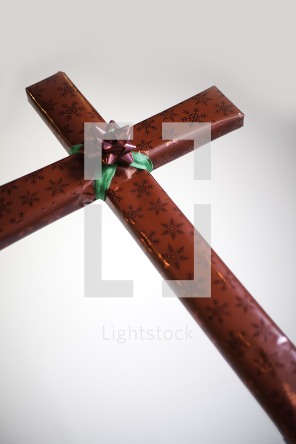 Red wrapped present  shaped like a cross with red and green bow in cenrer.