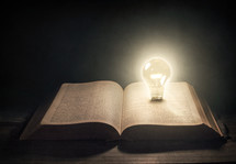 open Bible with lightbulb