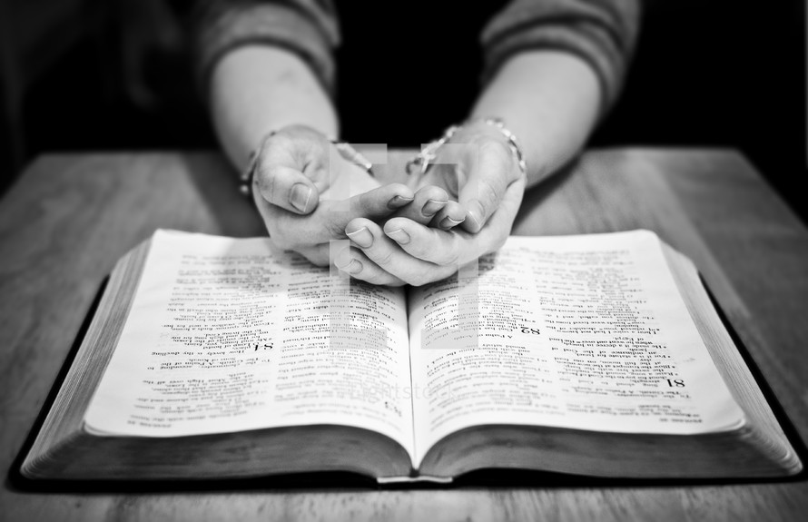 hands cupped in prayer over a Bible