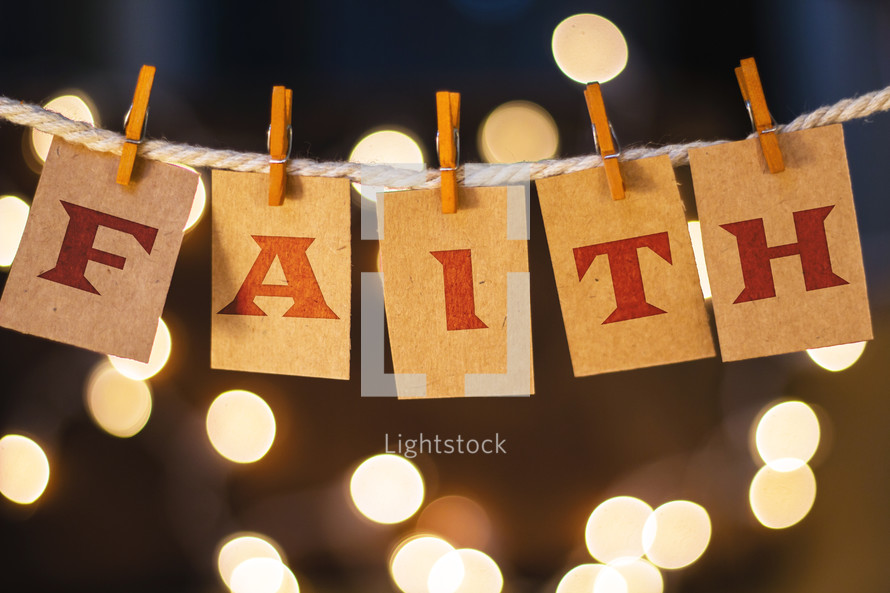 word faith hanging on clothes pins