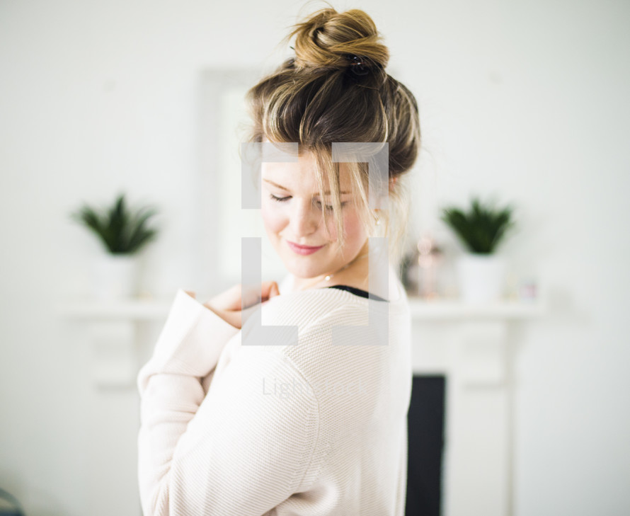 a woman with a bun looking down