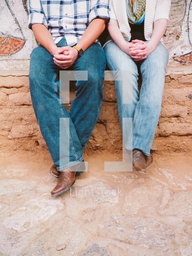 A couple wearing cowboy boots praying.
