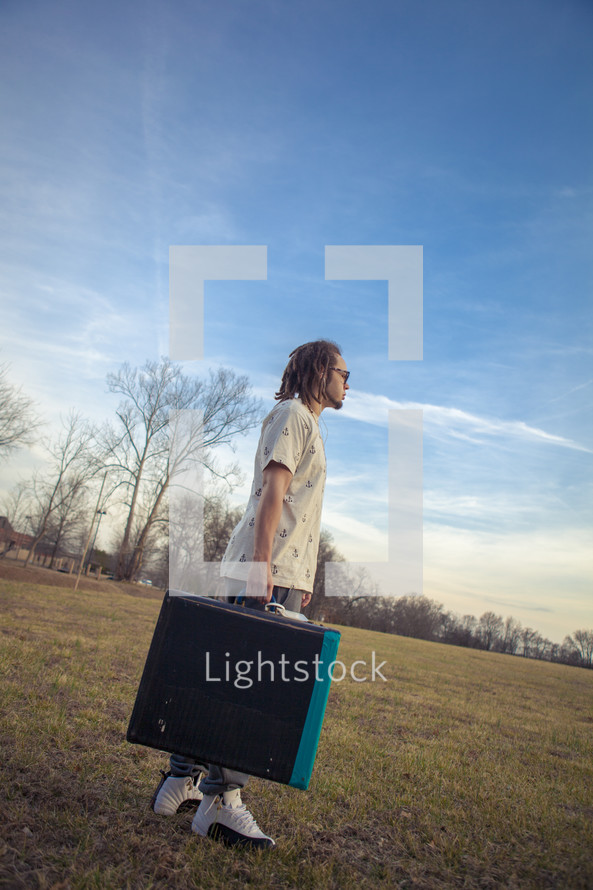 man with dreads carrying his art portfolio case