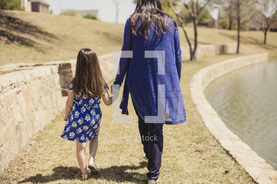 Mother and daughter holding hands while walking in the grass by a lake.