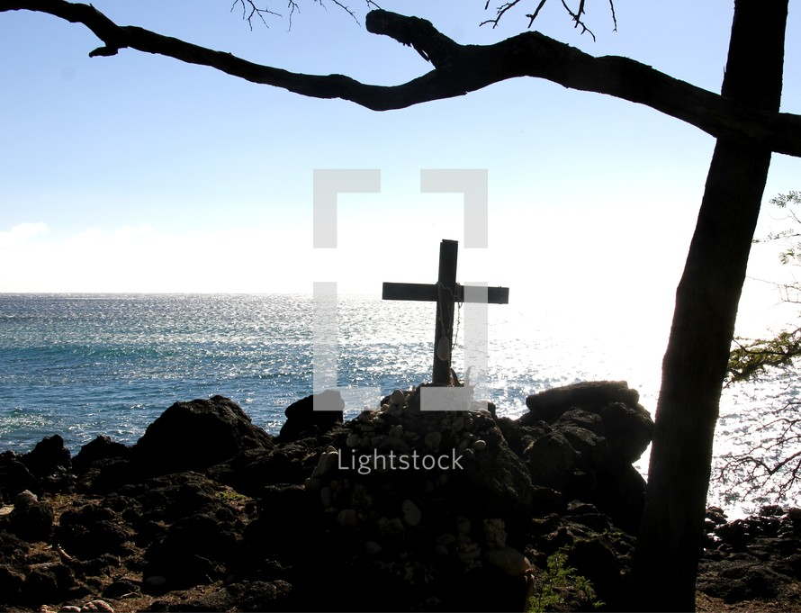 cross on a rocky cliff at the coast