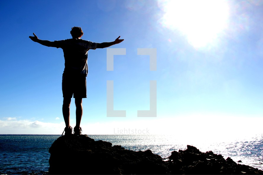 silhouette of a man with his arms outstretched on a sea cliff