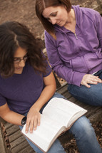 a woman and a young man reading a Bible - mentoring