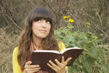 woman reading a Bible outdoors and looking up to God