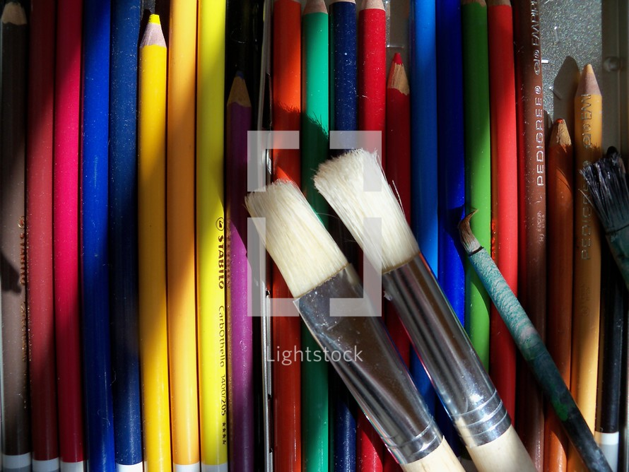 A set of colored pencils and varying sizes of paint brushes reflect an array of colors for an artist to crate illustrations, paintings, drawings and sketches to create a palette of colors to create a new piece of art.