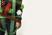 Mans's arm and torso tangled in red and green ribbon with bows stuck to him.