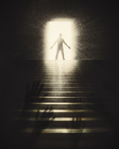 raised hands and a silhouette of a man standing in a doorway in sunlight