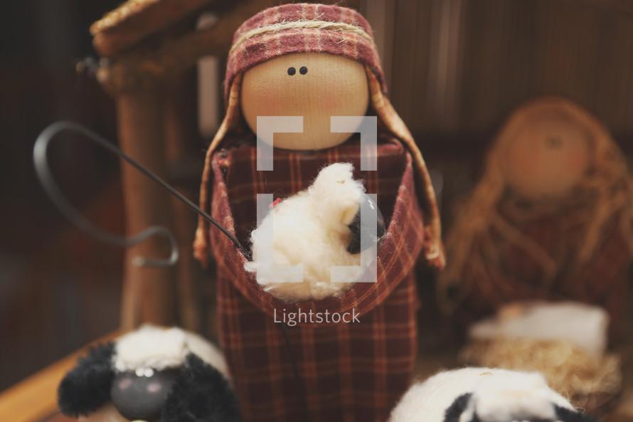 a hand made nativity scene - a shepherd and some sheep