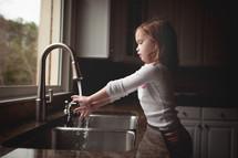 girl child washing her hands at a kitchen sink