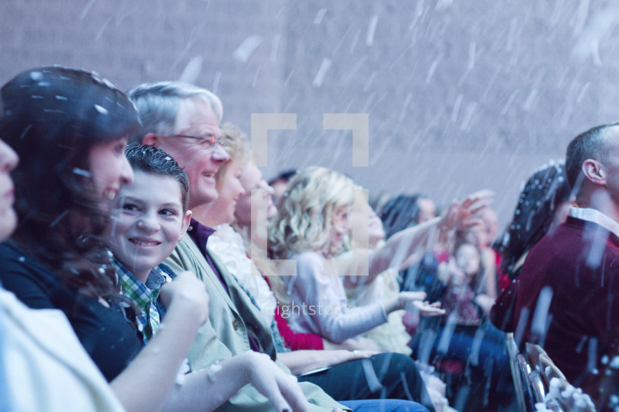 snow falling on a congregation during an outdoors worship service