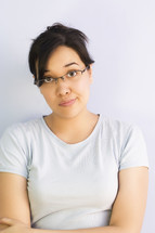 Close up image of skeptical Asian woman wearing glasses with her arms crossed