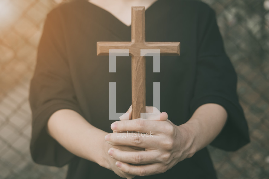 a woman holding a wooden cross