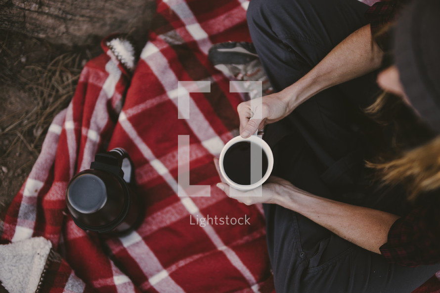 a person sitting on a blanket drinking coffee