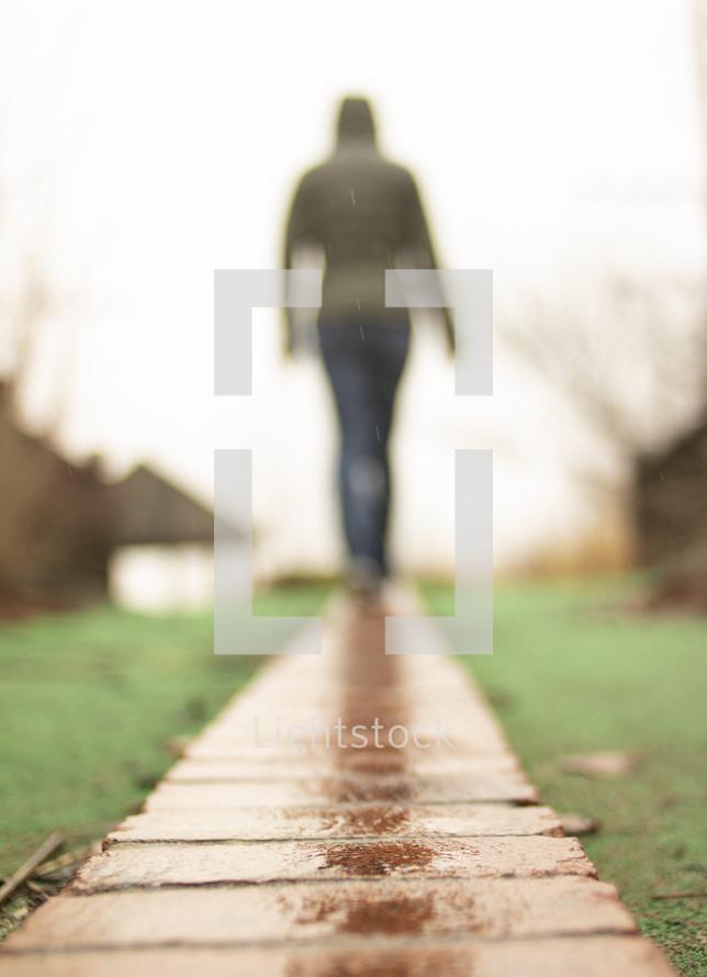woman walking over a wet boardwalk