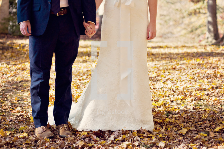legs of a bride and groom standing in fall leaves