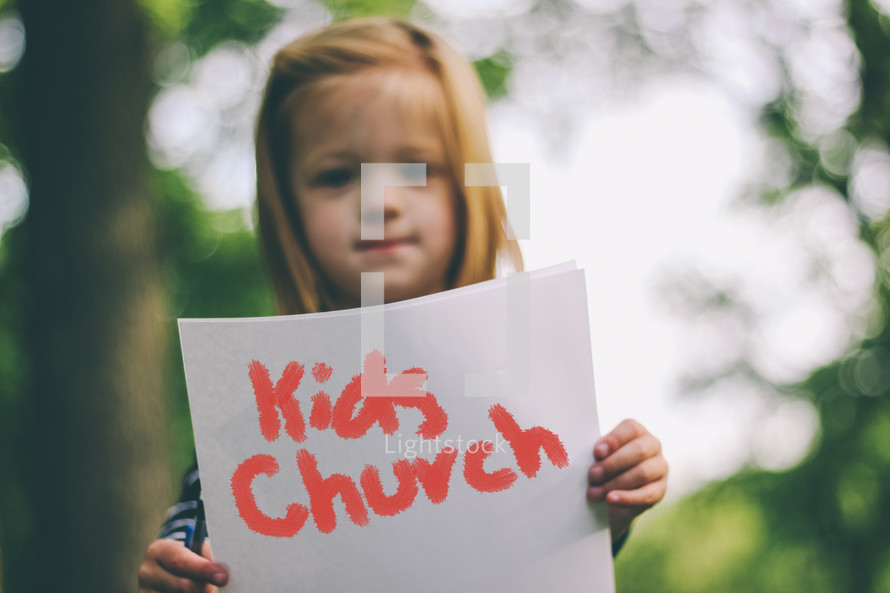 girl holding a Kid's Church sign