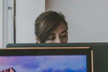 a woman behind a computer screen