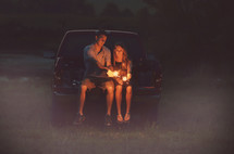 couple lighting sparklers on a tailgate