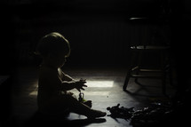 A toddler playing with toys on the floor.