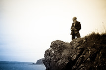 a man standing near the edge of a sea cliff