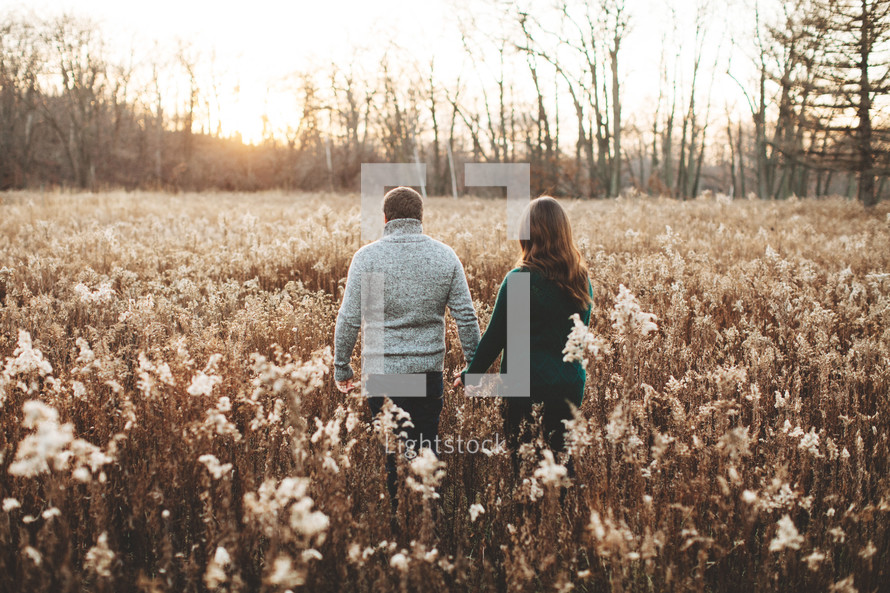 a couple standing in a field