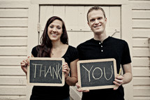 man and woman, standing in front of wood building holding thank you sign