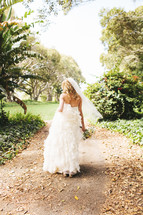 bride walking in in her bridal gown holding a bouquet along a path outdoors