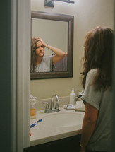 A young woman looking at herself in a mirror reflecting on her self image.