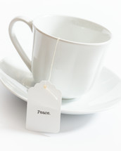 tea cup with the word peace on the tea bag