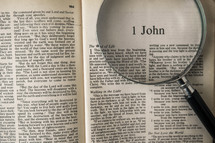 magnifying glass over Bible - 1 John