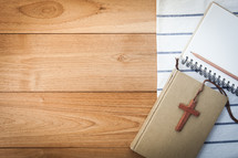 notepad, pencil, cross on a lanyard, and Bible on a wood table