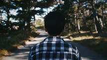 a young man walking down a paved path