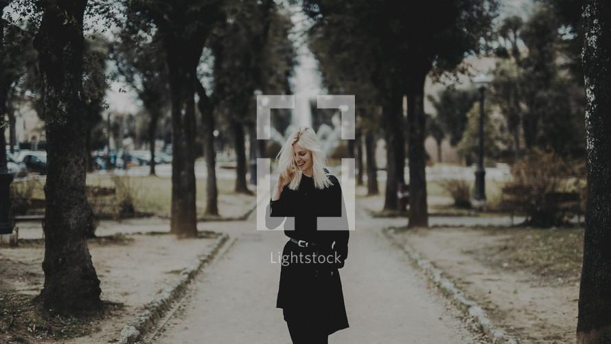 a blonde woman in a black trench coat walking down a sidewalk