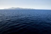 A dark ocean with an island in the horizon