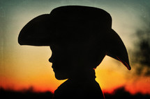 A silhouette of a young boy in a cowboy hat.