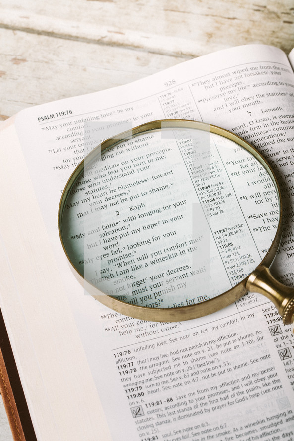Magnifying glass on top of page of Bible open to Psalm 119:81 laying on wooden table.
