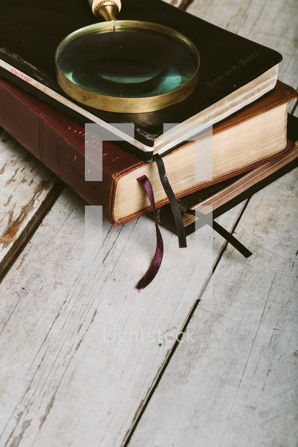 Magnifying glass on top of stack of massls and Bible on wooden floor.