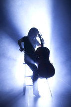 woman playing a cello under a spot light on stage