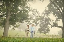 A woman leading a horse through a field.