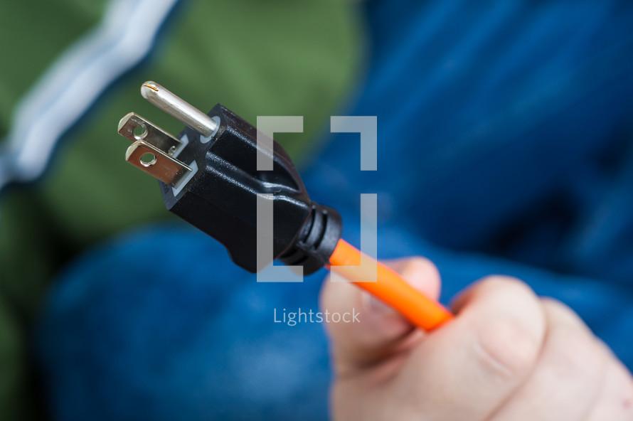 man holding a power cord plug