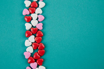 Small heart shaped candies lined up on an aqua background.