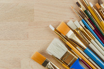 Many different sized paint brushes on a wooden table.