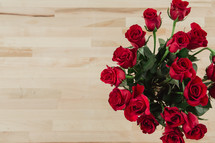 Red roses on a wood grain table.